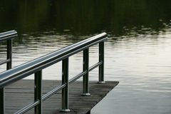 Pier at the waterside of the pond in the evening Stock Photos