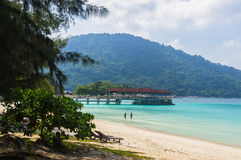 Pier on the white sand beach at Pulau Perhentian, Malaysia. Relax on a deserted beach in an island of Tropical paradise. Pier on the white sand beach at Pulau Royalty Free Stock Photos