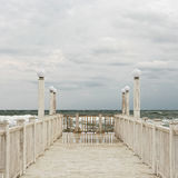 Pier with white wooden handrails at sea during a storm. Selective focus royalty free stock images