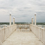 Pier with white wooden handrails at sea during a storm. Selective focus royalty free stock photos