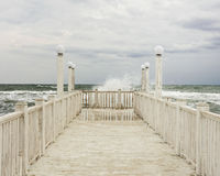 Pier with white wooden handrails at sea during a storm. Selective focus stock photography