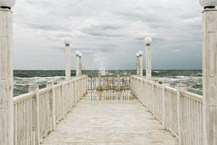 Pier with white wooden handrails at sea during a storm. stock images