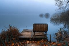 Pier on winter lake. Pier on winter foggy lake royalty free stock image