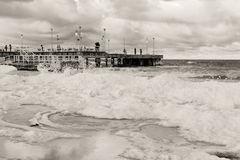 Pier in winter storm on the beach. Stock Image