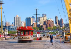 Pier 16 with woman walking and Brooklyn buildings skyline in daytime. Pier 16 is located east of South Street and FDR Drive in Low stock photo