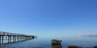 Pier with Wooden Boat. Deserted Pier with Wooden Boat Royalty Free Stock Images