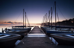 Pier and yacht on lake at sunrise Royalty Free Stock Photos