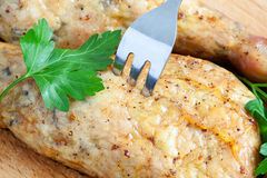 Pierce the chicken with a fork on a cutting board Royalty Free Stock Photography