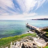 Pierce on the seashore in summer. Beautiful weather. people in the distance have a photo shoot. Nice travel location of Sozopol, Bulgaria Royalty Free Stock Photo