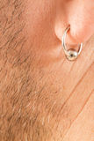 Pierced ear of a  man. Pierced ear of a mature man close-up short beard Stock Image