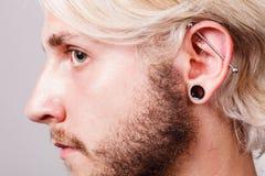 Pierced man ear, black plug tunnel, industrial and rook Stock Photo