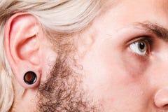 Pierced man ear, black plug tunnel Royalty Free Stock Image