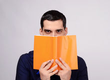 Piercing eyes looking over a notebook. Student holding a notebook. Royalty Free Stock Photo