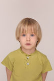 Piercing gaze of a boy. Portrait of a beautiful piercing gaze of a little blond man. Boy in yellow T-shirt with delicate white skin and blue eyes isolated on Royalty Free Stock Photo