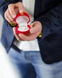 Pierścionek zaręczynowy lub teraźniejszość dawać męskimi rękami Zdjęcia Stock