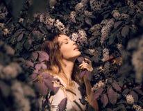 Pierda encima del retrato de una muchacha hermosa entre follaje y flores de la primavera foto de archivo libre de regalías