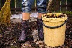 Pierna adolescente con la escoba floral de goma de las botas y compartimiento con las hojas secas viejas Imágenes de archivo libres de regalías