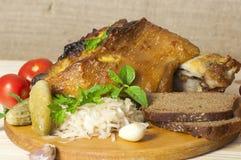 Pierna asada del cerdo servida con la chucrut Foto de archivo libre de regalías