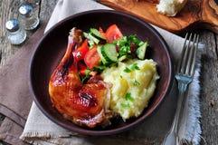Pierna de pollo asada esmaltada con la ensalada del puré de patata y vegetal en un fondo de madera Foto de archivo