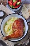 Pierna de pollo cocida con la ensalada del puré de patata y vegetal en una tabla de madera Foco selectivo Estilo rústico Fotos de archivo