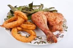 Pierna de pollo con las habas verdes y los anillos de cebolla Fotos de archivo