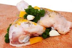 Pierna de pollo sin procesar con las hierbas, el ajo y la pimienta Imagen de archivo libre de regalías