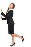 Pierna de Standing On One de la empresaria con las manos en la pared Fotografía de archivo