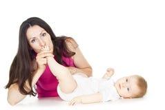 Pierna del bebé de la mama que se besa hermosa fotos de archivo libres de regalías