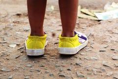 Pierna del bebé y situación blanca amarilla del zapato en una superficie concreta imagen de archivo