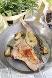 Pierna del conejo con las hierbas en una cacerola del brassr Fotografía de archivo