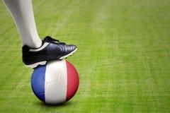 Pierna del jugador de fútbol con la bola en el campo Fotografía de archivo libre de regalías