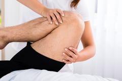 Pierna del ` s de Hand Massaging Man del terapeuta en balneario Foto de archivo