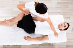 Pierna femenina joven del ` s de Massaging Relaxed Man del terapeuta imagen de archivo