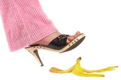 Pierna femenina (pie) y cáscara de un plátano. Seguro de vida. Imagen de archivo libre de regalías
