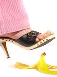 Pierna femenina (pie) y cáscara de un plátano. Seguro de vida. Foto de archivo libre de regalías