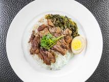 Pierna guisada del cerdo en el arroz con el huevo y el coto hervidos imagen de archivo