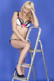 Pierna joven bochornosa de Pin Up Model Posing With en escalera de paso en tacones altos de la ropa interior Fotografía de archivo