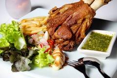 Pierna y patatas fritas fritas del cerdo. Fotos de archivo