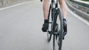 Piernas aptas flacas del ciclista con los músculos fuertes pedaling cuesta arriba de la silla de montar Entrenamiento de ciclo as metrajes