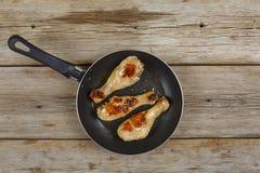 Piernas asadas a la parrilla pollo Piernas de pollo frito en un sartén en una tabla de madera, visión superior Foto de archivo