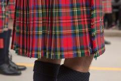 Piernas ascendentes cercanas masculinas de la falda escocesa que llevan Foto de archivo