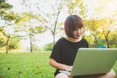 Piernas asiáticas jovenes del ` s de la mujer en la hierba verde con el ordenador portátil abierto Manos del ` s de la muchacha e Fotografía de archivo libre de regalías