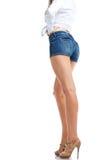 Piernas atractivas de la mujer en los pantalones cortos de la mezclilla, aislados en el fondo blanco Imágenes de archivo libres de regalías