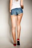 Piernas atractivas de la mujer en pantalones cortos de la mezclilla foto de archivo