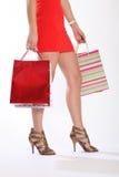 Piernas atractivas de la mujer que recorren con los bolsos de compras Imagen de archivo libre de regalías
