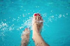 Piernas atractivas de las mujeres que salpican en piscina tropical foto de archivo