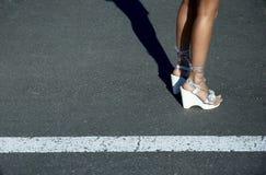 Piernas atractivas en sandalias Foto de archivo libre de regalías