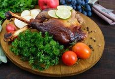 Piernas cocidas del ganso, servidas con las manzanas, verduras, uvas, verdes en una bandeja redonda del roble Fotos de archivo libres de regalías