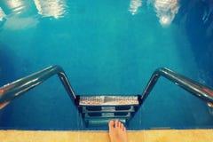 piernas con en la piscina azul Fotografía de archivo
