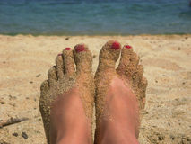 Piernas con la arena en la playa foto de archivo